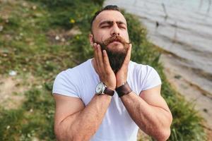 amerikanischer bärtiger Mann, der seinen Bart berührt foto