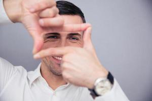 Geschäftsmann, der Rahmen mit den Fingern macht foto