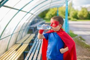 Superheld steht unter Baldachin und trinkt Wasser aus einer Flasche foto
