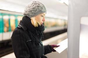 Dame, die auf Kartenfeld des öffentlichen Verkehrs schaut.