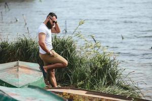amerikanischer bärtiger Mann, der Telefon nahe dem Fluss benutzt foto