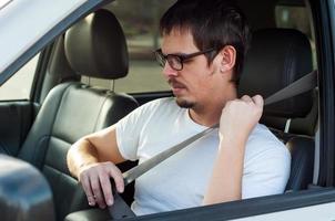 männlicher europäischer Fahrer benutzt Sicherheitsgurt in einem Auto