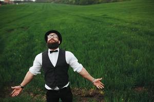 Mann mit Bart, der auf dem Feld denkt foto