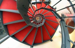 Wendeltreppe mit rotem Teppich für einen schwindelerregenden Aufstieg foto