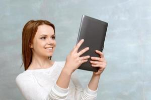 lächelnde junge Frau, die mit Tablette steht foto