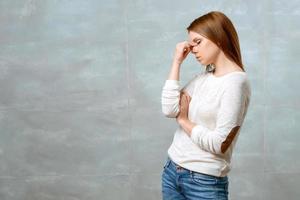 Frau steht und berührt den Nasenrücken foto