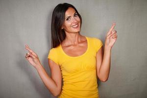 charismatische Frau, die beim Wünschen die Daumen drückt foto