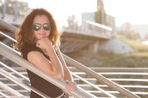 schöne lächelnde junge Frau, die sich auf einen Zaun stützt foto