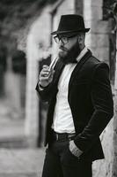 reicher Mann mit Bart raucht elektronische Zigarette foto
