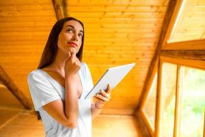 Frau denkt mit digitaler Tablette im Holzhaus
