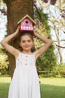 Mädchen hält Vogelhaus auf dem Kopf foto