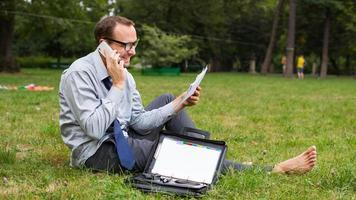 Geschäftsmann sitzt auf einem Gras und plaudert foto