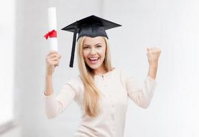 glückliches Studentenmädchen in der Junggesellenkappe mit Diplom foto