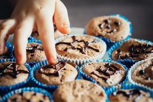 Kinderhand berührt das Sahnehäubchen auf Cupcakes foto