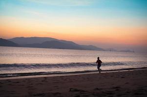 Mann läuft am Strand foto