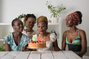 Mädchen, das Geburtstagstorte betrachtet, umgeben von Freunden foto