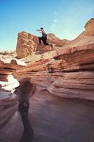 tapferer Mann, der über die Klippe im Canyon springt foto