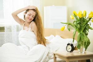 Frau wacht im Bett auf foto