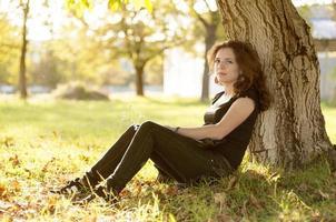 schöne junge Frau, die auf Gras unter dem Baum sitzt foto