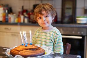 entzückender vierjähriger Junge, der seinen Geburtstag feiert foto