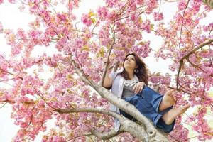 Frühlingsblüten halten ein sich wunderndes Mädchen foto