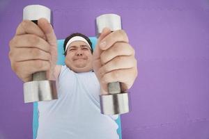übergewichtiger Mann, der Hanteln hebt foto