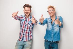 zwei glückliche junge lässige Männer, die das OK-Zeichen machen