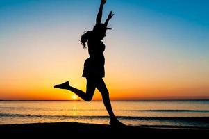 Silhouette der Frau, die in die Luft springt