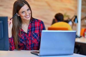Porträt der Geschäftsfrau, die beim Sitzen durch Kollegen im Büro lächelt foto