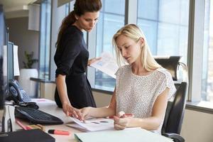 Geschäftsfrauen, die am Schreibtisch am Computer zusammen arbeiten foto