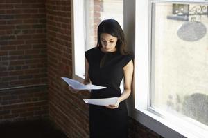 Geschäftsfrau liest Dokument, das durch Bürofenster steht