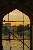 See Pichola in der Abenddämmerung von einem Torbogen, Indien eingerahmt foto