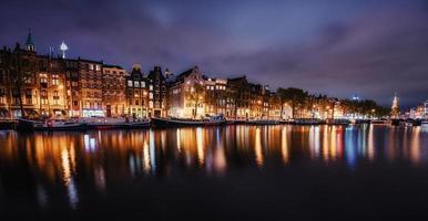 schöne nacht in amsterdam. Nachtbeleuchtung von Gebäuden an foto