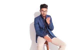 Mann im Anzug sitzt auf einem Stuhl und gestikuliert foto