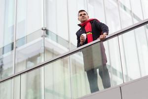 zufrieden verträumter junger Mann mit Kaffeetasse, der in die Ferne schaut foto
