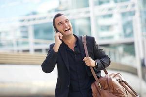 glücklicher Mann, der in der Stadt mit Handy und Tasche geht foto