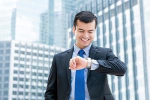 Geschäftsmann lächelt und schaut auf seine Armbanduhr mit einem glücklichen Moment in der Stadt foto