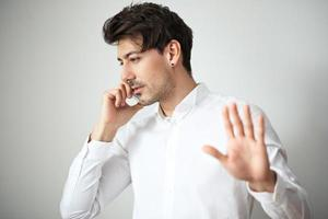 junger Mann spricht am Handy foto