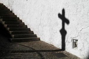 Schatten eines Kreuzes mit einer Treppe foto