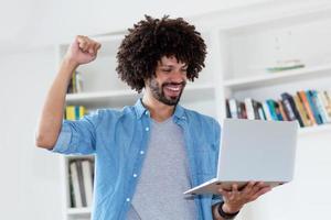 jubelnder Hipster-Mann mit Afro-Haaren und Computer