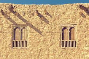 zwei Bogenfenster auf einer alten Steinmauer. foto