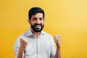 Porträt eines zufriedenen jungen Mannes, der lokal über gelbem Hintergrund feiert foto