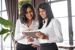 zwei lächelnde Kolleginnen, die Nachrichten auf Tablette im Café lesen foto