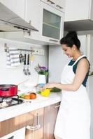 Inderin, die in der Küche kocht foto