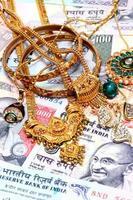 Nahaufnahme von Goldschmuck auf indische Währung