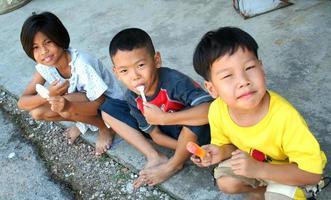 Drei Kinder essen Eis am Stiel auf der Straße foto