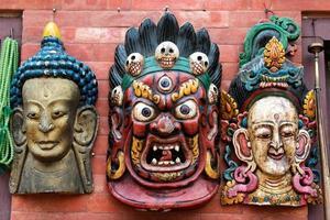 Drei traditionelle hinduistische Masken hängen an der Wand in Kathmandu Souve