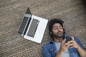 asiatischer Mann, der auf dem Boden mit Laptop und Telefon liegt. foto