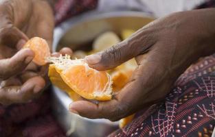 Hände der indischen Frau, die Mandarine schält