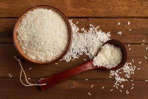 Reis in Keramikschale und Löffel auf einem Holztisch foto